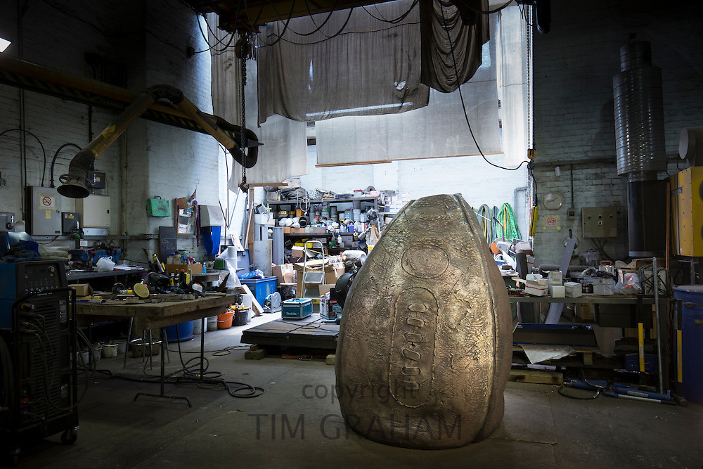 Bronze rubgy ball sculpture by artist Gavin Turk photographed at a foundry in East London. The sculpture is destined for installation at Rugby School - the birthplace of rugby ----------COPYRIGHT - TIM GRAHAM. For permission to use  this image please contact mail@timgraham.co.uk