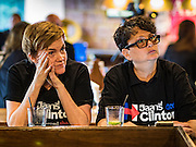 09 NOVEMBER 2016 - BANGKOK, THAILAND:  Women wearing Hillary Clinton / Democrats Abroad Thailand tee shirts watch election results come in Wednesday morning (Thai time) in Bangkok. Democrats Abroad Thailand met at the Roadhouse Barbecue, an American restaurant in Bangkok, to watch election results come in. It was a somber election watch party as what was expected to be a Clinton victory turned into a Trump win.     PHOTO BY JACK KURTZ