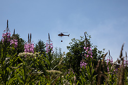 © Licensed to London News Pictures . 03/07/2018. Bolton, UK. A helicopter organised by the Woodland Trust, a fifth of whose land at Smithills Estate on Winter Hill has been burned in the fire, picks up water from reservoirs and dowses the fire as part of a combined firefighting effort. Fire-fighters continue to work to contain large wildfires spreading across Winter Hill as very high temperatures , changing winds and dry peat continue to exacerbate the problem . Photo credit: Joel Goodman/LNP