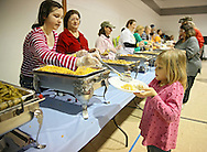 Lilly Proper (from left), 12, of Marion, serves corn to Paisley Miller, 7, of Cedar Rapids during the HD Center Christmas party at Metro High School, 1212 7th St. SE in Cedar Rapids on Saturday, December 22, 2012. About 60 volunteers helped at the event.
