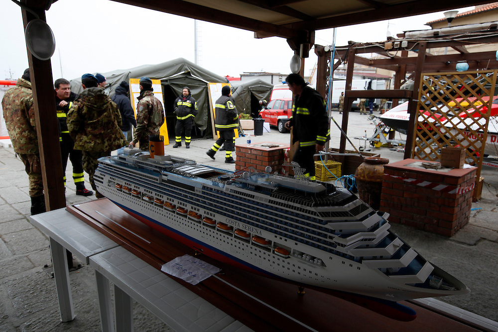 Firefighters walk past a model of the cruise ship Costa Serena, sister ship to the cruise liner Costa Concordia, at Giglio island January 31, 2012. Italian authorities have ended the search for bodies on the submerged sections of the capsized Costa Concordia, more than two weeks after the giant cruise liner capsized off the Tuscan coast, officials said on Tuesday...REUTERS/Darrin Zammit Lupi (ITALY)