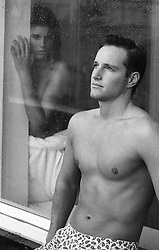 shirtless woman looking at a shirtless man through a large window