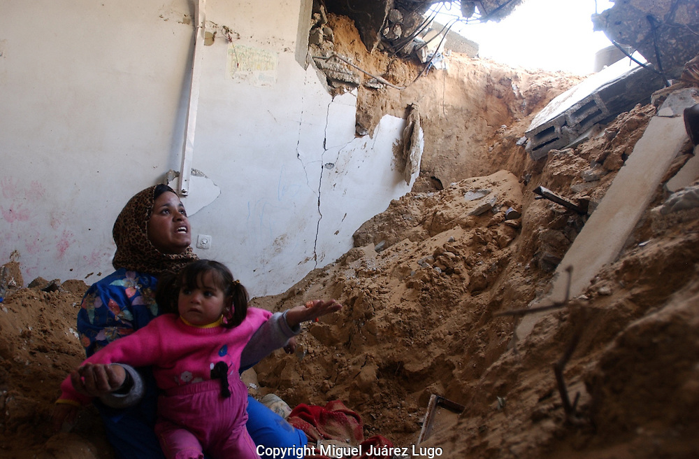 Gaza, Palestine. Najat El Louh, 32, mother of ten, with 3 year old Sarah, asks God from an explanation in why she has to lost everything from a place once was her house.  Two weeks after the Israeli military campaign inside Gaza many people is starting to asset the size of the damage. (PHOTO: MIGUEL JUAREZ)