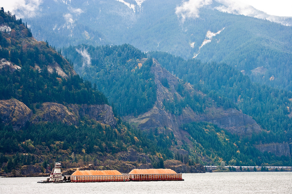 A tugboat pushes barges filled with wood chips downstream through the Columbia River Gorge between Oregon and Washington, USA.