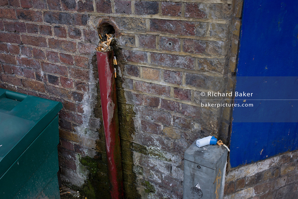 An inhaler and discarded cigarettes spill from a hole in a brick wall in Waterloo, south London.
