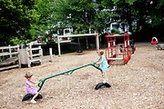 """Identical twin sisters Piper (purple) and Katie, 5, play at McClatchey Park in Atlanta May 14, 2010. Piper said the best part about having a sister is """"giving my sister hugs and kisses."""" Katie said the best part about having a sister is """"kissin' her and huggin' her."""""""