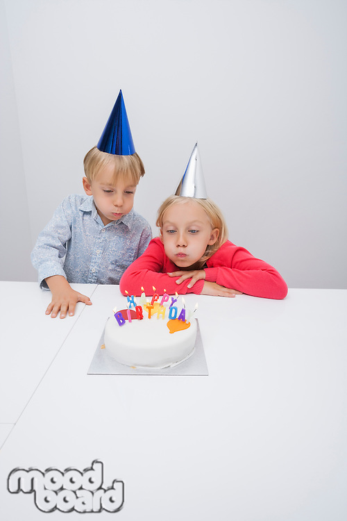 Siblings blowing birthday candles at table in house