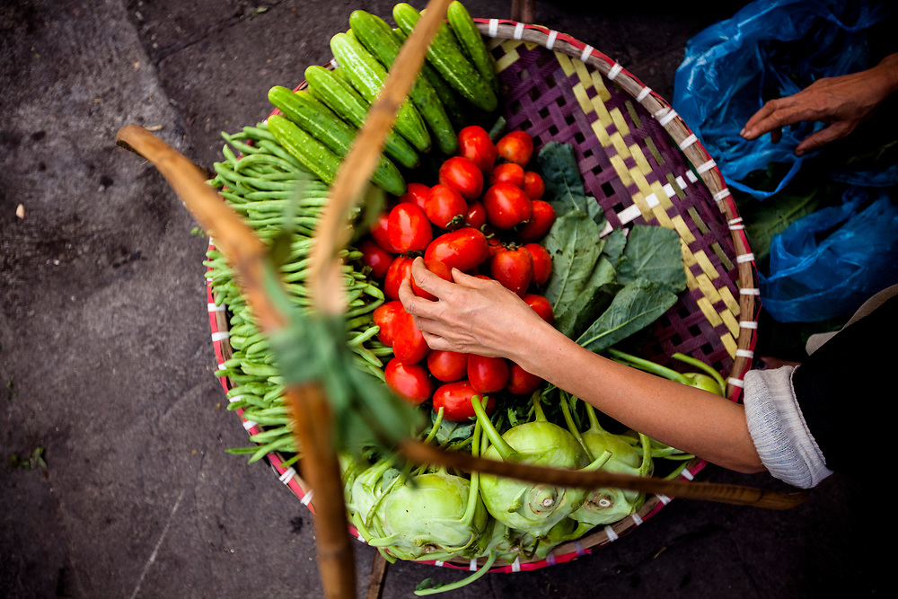 A street seller arranges her vegetables for sale out of a basket in Hanoi, Vietnam.