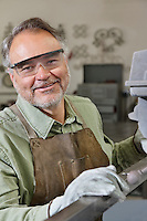 Portrait of happy mature metalworker wearing protective eyewear in workshop