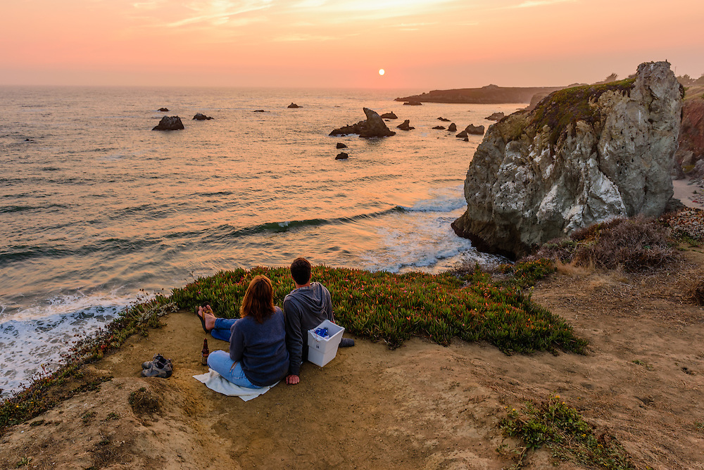 Couple looking at sunset, Sonoma Coast State Beach, Jenner,, California
