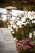 Cobblestone Column With White Fence And Flowers