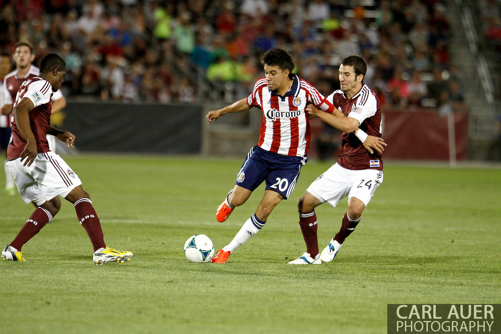 May 25th, 2013 Commerce City, CO - Chivas USA midfielder Carlos Alvarez (20) dribbles the ball against the defense by Colorado Rapids midfielder Nathan Sturgis (24) in the second half of the MLS match between Chivas USA and the Colorado Rapids at Dick's Sporting Goods Park in Commerce City, CO