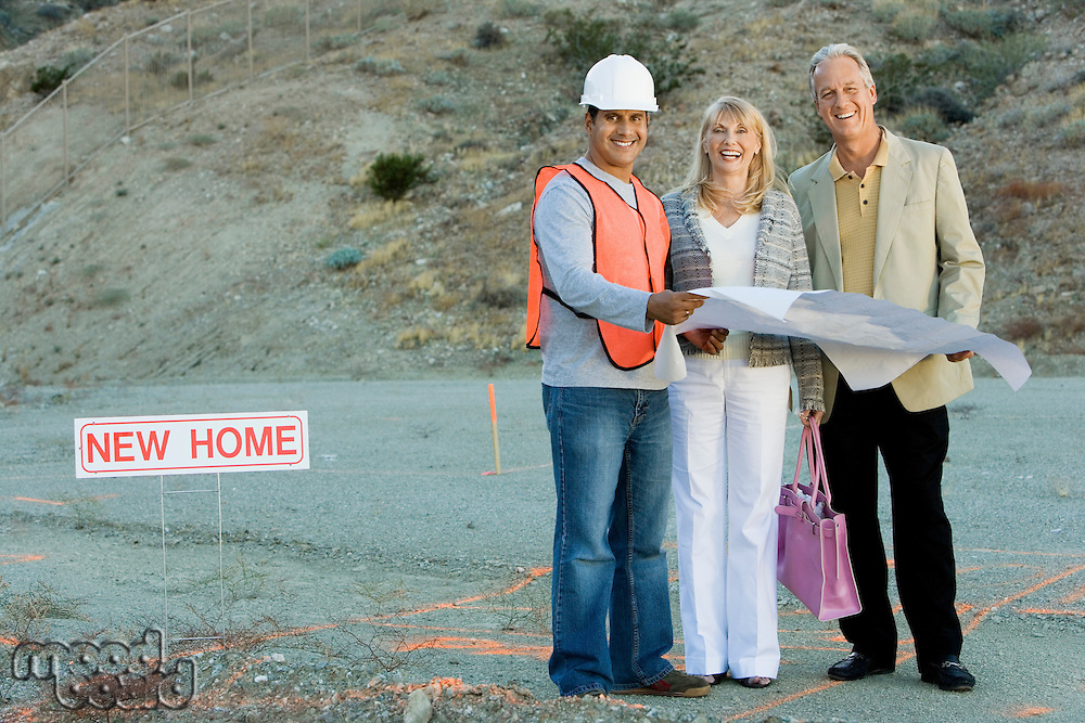 Builder and Couple at New Home Construction Site