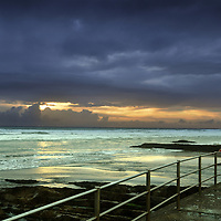 Dramatic sunset in Cornwall, England with teenage girl looking out to sea