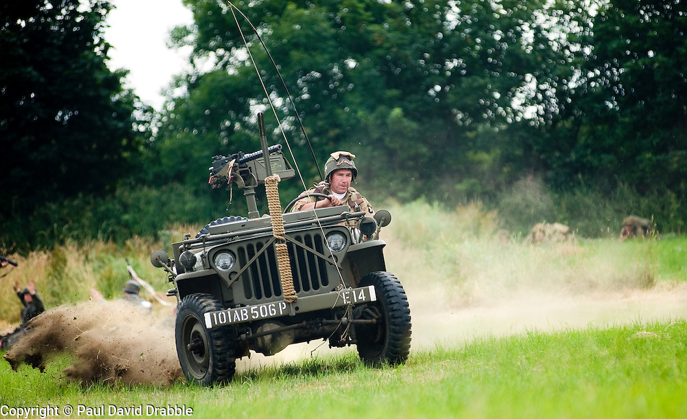 "Re-enactor from the Northern World War Two Association Living History group portraying a member of the American 101st Airborne ""Screaming Eagles"" speeds across the battlefield in a Willys Jeep mounted with a Browning 30 caliber machine gun during a large scale battle re-enactment. SPAM 1940's Weekend. Heckmonwyke near Wakefield 10 July 2010 .Images © Paul David Drabble."