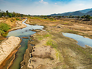 31 MARCH 2016 - NONG LONG, LAMPHUN, THAILAND:  The nearly empty Ping River in Lamphun province. The Ping River runs through northern Thailand and is the most important river in the area. People who live along the river said it has never been this low. Normally there is more than a meter of water across the river bottom at this part of the river at this time of year.  People are building small mud dams and catchments along the river bottom to try to keep some water and fish in it.     PHOTO BY JACK KURTZ