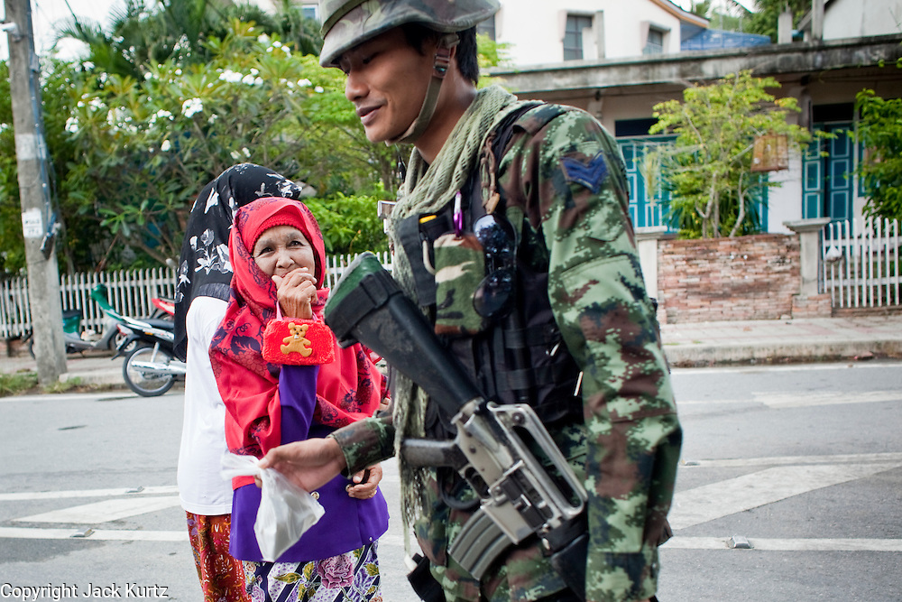 """Sept 26, 2009 -- PATTANI, THAILAND:  A Thai soldier accepts a drink from a Muslim woman during a Thai army security operation near Krue Se Mosque in Pattani, Thailand, Sept 26. Thailand's three southern most provinces; Yala, Pattani and Narathiwat are often called """"restive"""" and a decades long Muslim insurgency has gained traction recently. Nearly 4,000 people have been killed since 2004. The three southern provinces are under emergency control and there are more than 60,000 Thai military, police and paramilitary militia forces trying to keep the peace battling insurgents who favor car bombs and assassination.   Photo by Jack Kurtz / ZUMA Press"""