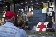 Visitors look at an exhibit that includes photos, letters, and memorabilia from the Vietnam War in Bicentennial Park on September 15, 2017.