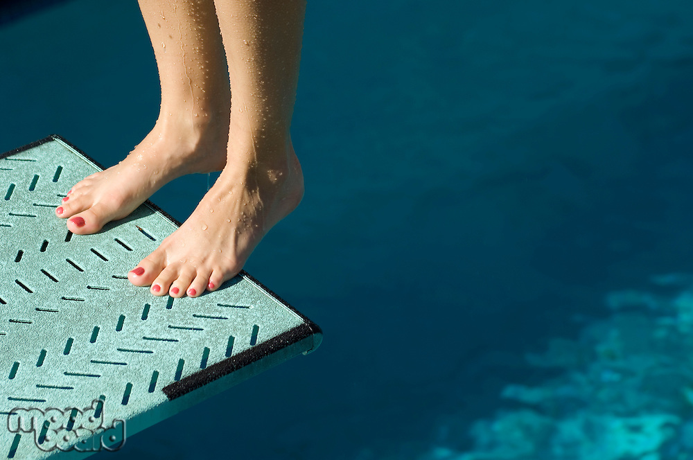 Female swimmer standing on diving board