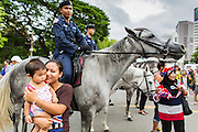 "15 JUNE 2014 - BANGKOK, THAILAND: Thais pose for pictures with members of the Royal Thai Police mounted police unit during a ""Return Happiness to Thais"" party in Lumpini Park in Bangkok. The Thai military junta, formally called the National Council for Peace and Order (NCPO), is sponsoring a series of events throughout Thailand to restore ""Happiness to Thais."" The events feature live music, dancing girls, military and police choirs, health screenings and free food.   PHOTO BY JACK KURTZ"