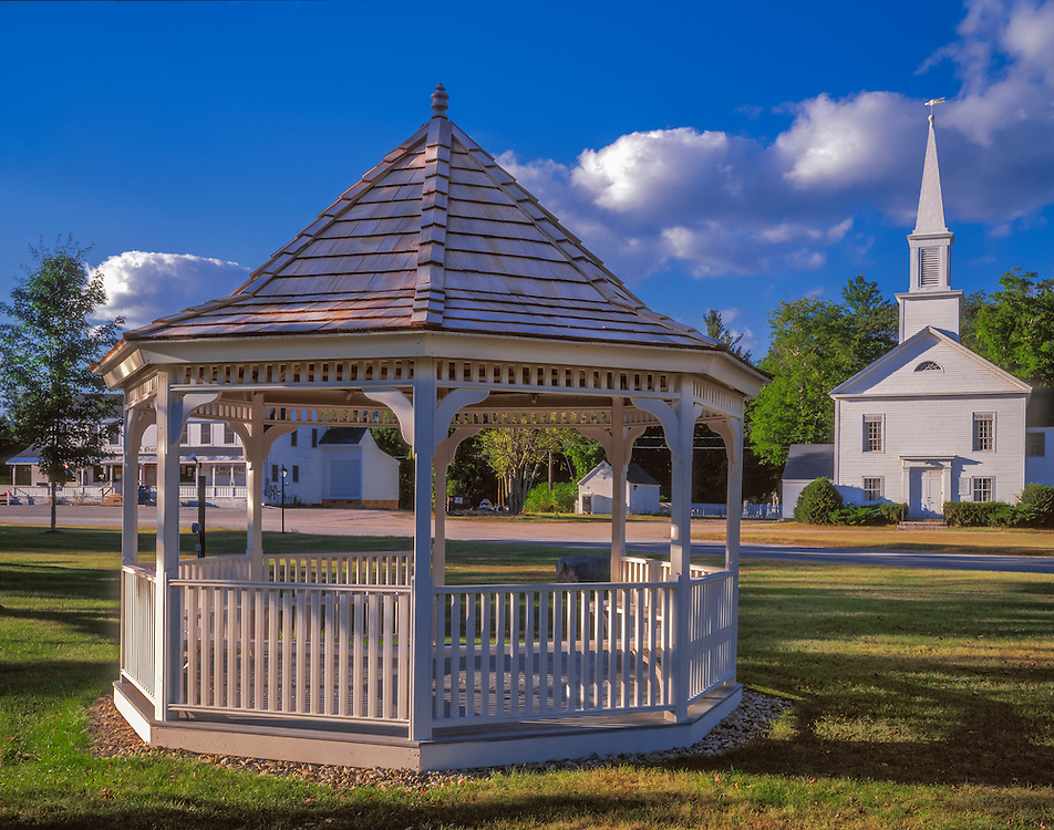Gazebo on village green in summer, church beyond, Hebron, NH