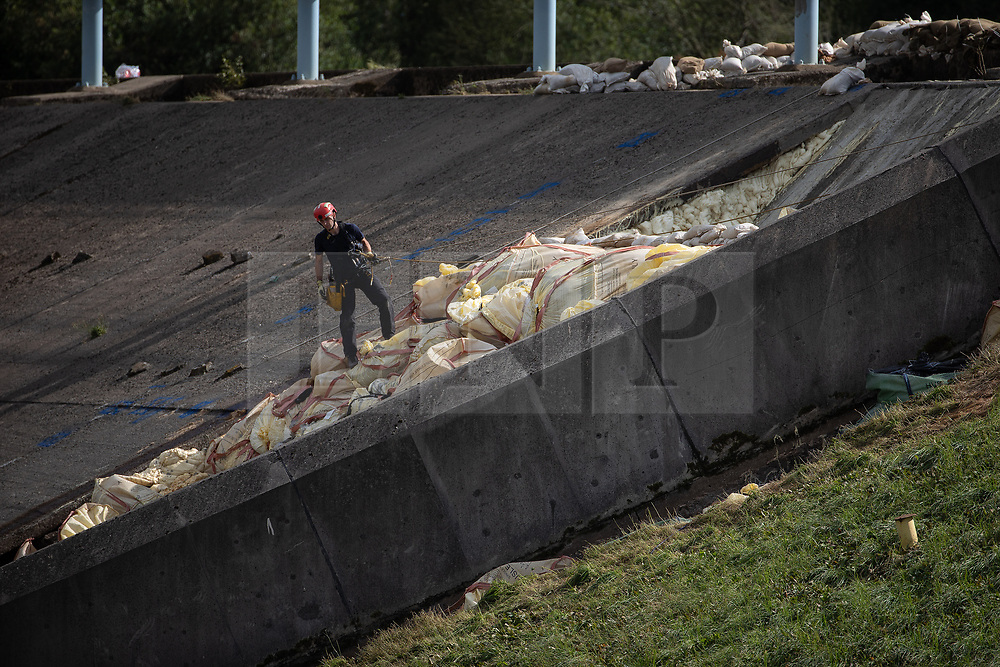 © Licensed to London News Pictures. 05/08/2019. Whaley Bridge, UK. A man wearing climbing kit abseils down the damaged area of the reservoir's slipway . The town of Whaley Bridge in Derbyshire remains evacuated after heavy rain caused damage to the Toddbrook Reservoir , threatening homes and businesses with flooding . Photo credit: Joel Goodman/LNP