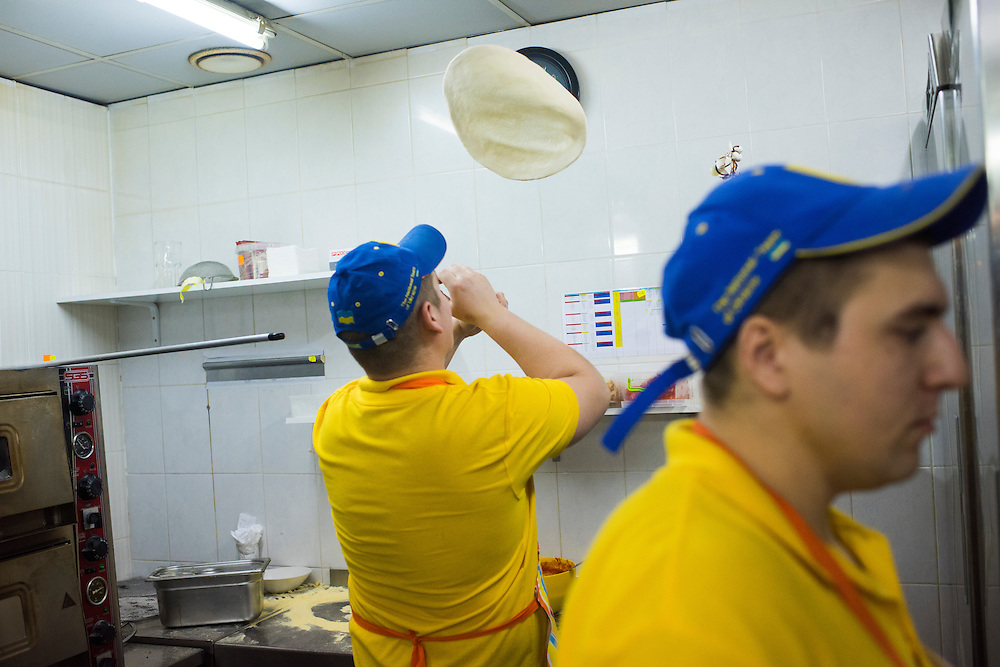 Artyom Rudenko tosses a pizza crust as Mikhail Yora, right, cleans up the kitchen at Veterano Pizza on January 24, 2016 in Kiev, Ukraine. (Pete Kiehart for The New York Times)