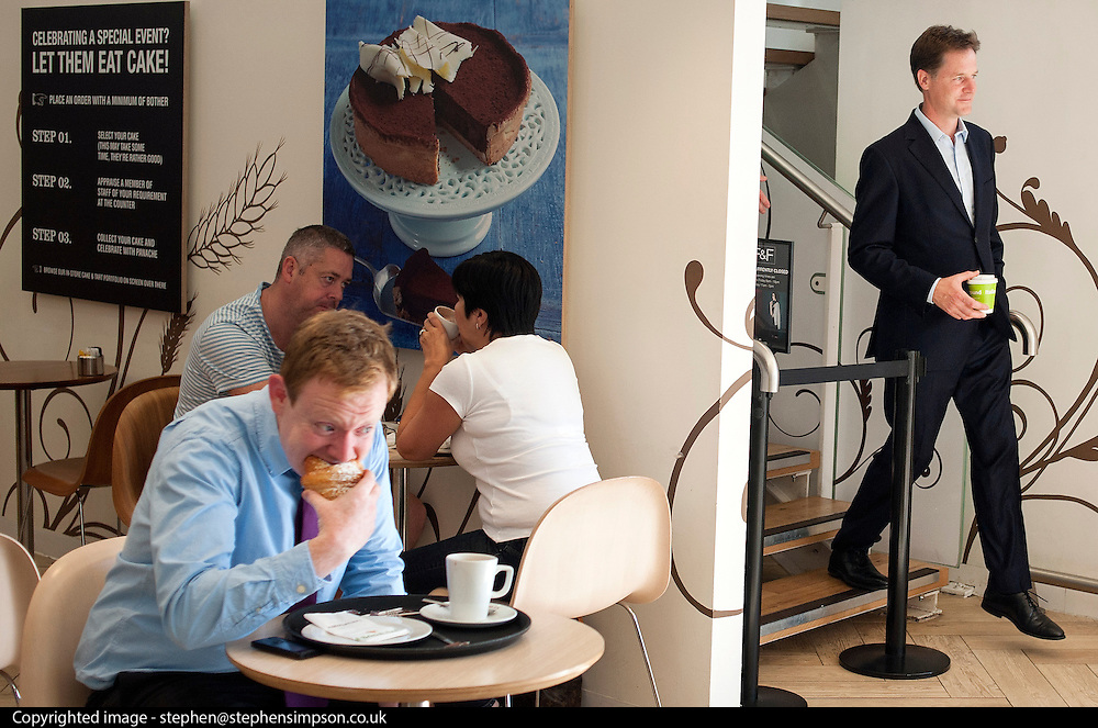 ***EMBARGO UNTIL 0001 FRIDAY 18th JULY 2014***© Licensed to London News Pictures. 16/07/2014. London, UK. A man eats a cake as NICK CLEGG leaves the cafe at the store.  Deputy Prime Minister and Leader of the Liberal Democrats Nick Clegg visits Tesco in Kensington to meet staff along with Jo Swinson. The Liberal Democrats will say in their 2015 manifesto that they will require large companies to publish the average salary of their male and female employees, increasing public pressure for equal pay. Tesco are one of the companies that currently publish this information voluntarily under the Government's Think, Act, Report scheme.. Photo credit : Stephen Simpson/LNP