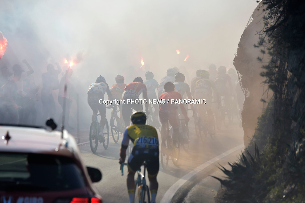 Illustration picture of the peloton passing some fans with fireworks during the UCI WorldTour 107th Milano - Sanremo cycling race with start in Milano and finish at the Via Roma in Sanremo in Sanremo, Italy.<br /> *** SANREMO, ITALY - 19/03/2016