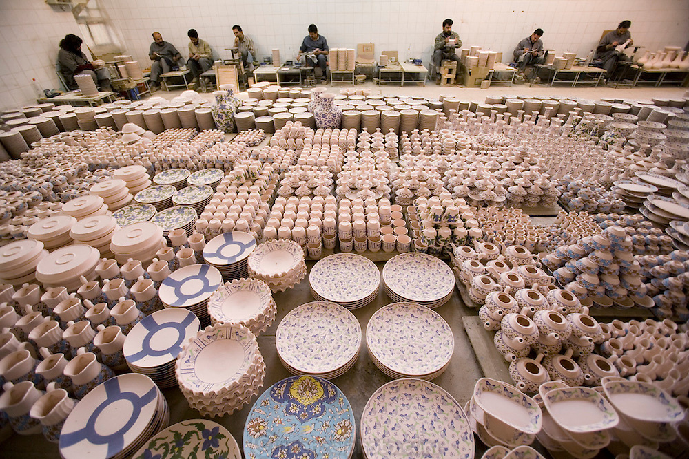 "Painters, each with his own traditional design assignment applies color to bisqueware at Morvarid (Pearl) Pottery Factory, Meybod,  Iran. (Also spelled ""Maybod"")."