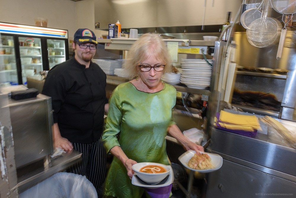 Kathy Cary expedites a food order as she helps out in the back before joining her visiting family in the dining room. In the kitchen during dinner at Lilly's, Wednesday, Aug. 17, 2016 with Chef/Owner Kathy Cary's staff. (Photo by Brian Bohannon)