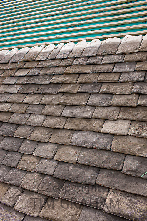 Re-roofing with reproduction Cotswold roof slates a Cotswolds stone property using traditional method of tiling and cardinal slates, UK