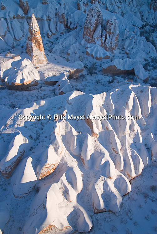 Goreme, Nevsehir, Cappadocia, Turkey. Hot air Balloons fly over the valleys of Cappadocia. A fresh pack of snow has turned the winter landscape of Goreme National Park into an even bigger fairy tale. Photo by Frits Meyst/Adventure4ever.com