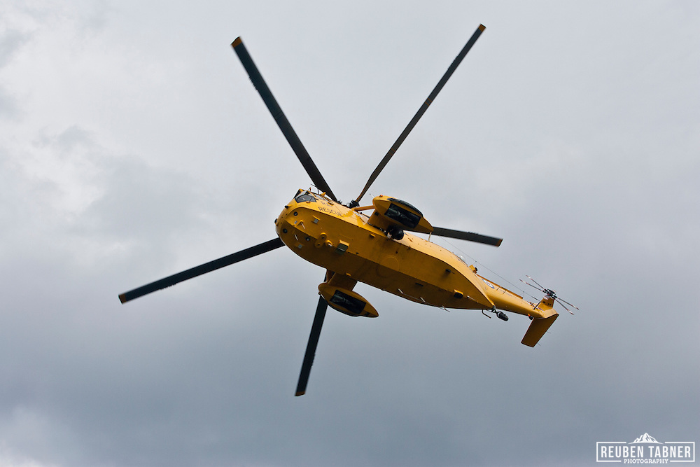 A yellow, RAF rescue Sea King Helicopter hovers, over Staithes, North Yorkshire, England.