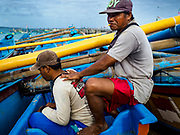 03 AUGUST 2017 - KUTA, BALI, INDONESIA: A fish market porter gives his friend a back rub while they wait for work on Jimbrana Beach in Kuta. The beach is close to the airport and a short drive from other beaches in southeast Bali. Jimbrana was originally a fishing village with a busy local market. About 25 years ago, developers started building restaurants and hotels along the beach and land prices are rising. The new emphasis on tourism is changing the nature of the area but the fishermen are still busy very early in the morning.     PHOTO BY JACK KURTZ