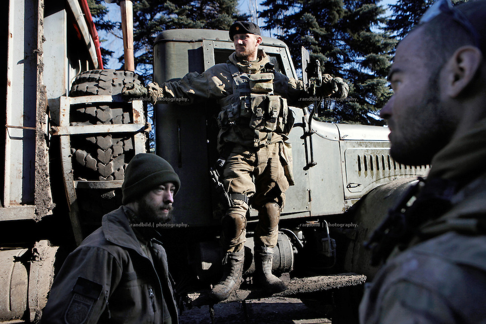 An ukrainian militia stands on a Prway Sector truck returning from the frontline to the base of the right-wing organisation. Alex (le.) and Cowboy (ri.) get ready to unload the truck. <br />