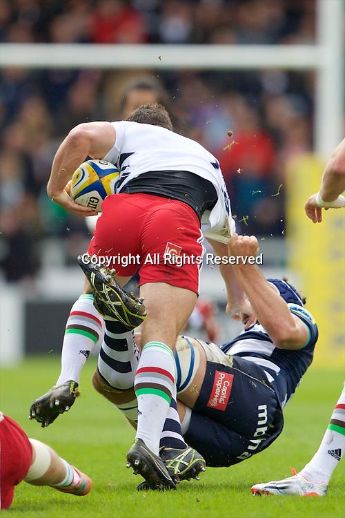 25.04.2015.  Sale, England.  Aviva Premiership Rugby. Sale Sharks versus Harlequins. Harlequins centre George Lowe hands off to Sale Sharks lock Josh Beaumont.