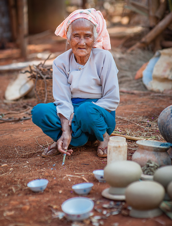 Old woman smoking a cigar at pottery barn (Myanmar)