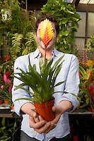 Man Holding Out a Tropical Plant