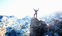 Man stands with hands above his head on the summit of Prusik Peak in the Enchanted lakes Wilderness Area, Washington Cascades, USA.