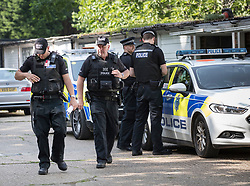 © Licensed to London News Pictures. 26/05/2018. Crawley, UK. Police officers are seen at some garages near a block of flats in Crawley where a woman was found dead.  A man has been arrested on suspicion of murder after the woman was found in her bed. Police are appealing for witnesses to come forward.  Photo credit: Peter Macdiarmid/LNP