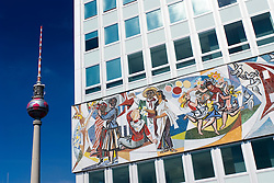 Socialist murals on the Haus des Lehrers - House of Teachers- with television tower to rear at Alexaderplatz in Berlin Germany 2009