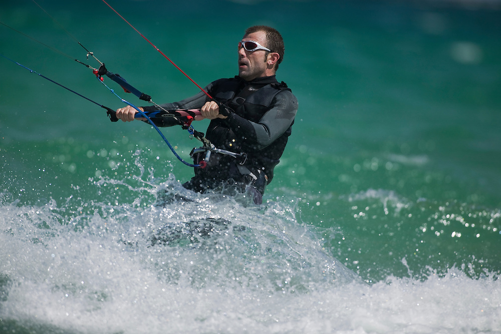 South Africa, Western Cape Province, Cape Town, (MR) Kite surfer rides through breaking waves at Fish Hoek Beach near Simon's Town