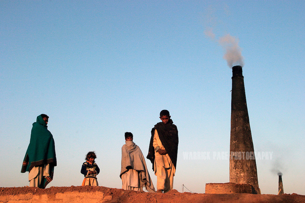 "Child labourers gather in the morning sun at the brick kiln where they work 7 days a week on the outskirts of Rawalpindi, December 3, 2004, Rawalpindi, Pakistan. Tens of thousands of Pakistani children are born into bonded labour, put to work in order to pay off recurring family debts. The UN describes bonded labour, or 'debt bondage', as modern-day slavery and it is prohibited under international law. Despite its prohibition, Anti-Slavery International estimates ""between 10 and 20 million people are being subjected to debt bondage today"". Bonded labour is all-too common in developing nations where landlords and tribal systems rule with impunity. (Photo by Warrick Page)"