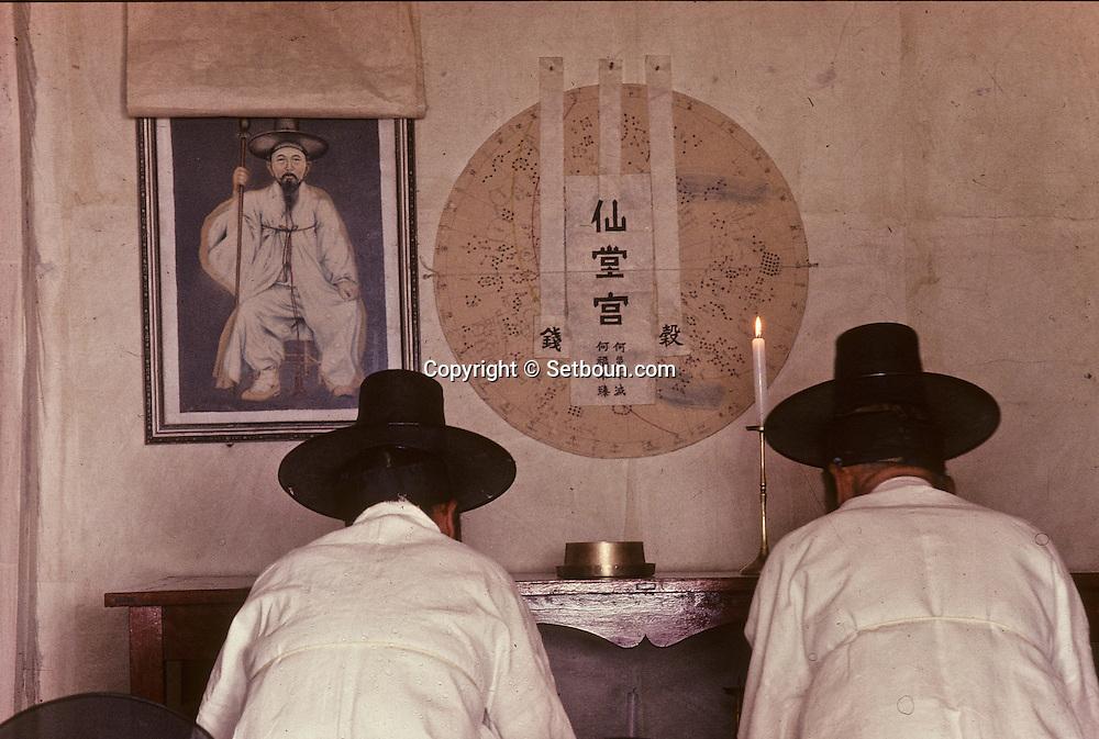 Chonhakdong traditional confucianist village  Prayer before the altar. The cup of water Chonhakdong traditional confucianist village  is a symbol for purity. The great circle represents the universe. The portrait of Kang Tae Song, the foundator of this religion, is unveiled on the occasion of the ceremony.    Korea   village traditionnel confucianiste de Chonhakdong  La prière devant l'autel; la coupe d'eau est symbole de purete; le grand cercle represente l'univers. Le portrait de Kang Tae Song, le fondateur de cette religion, n'est devoile que pour la ceremonie.    Coree  //////R28/28    L2645  /  R00028  /  P0003022