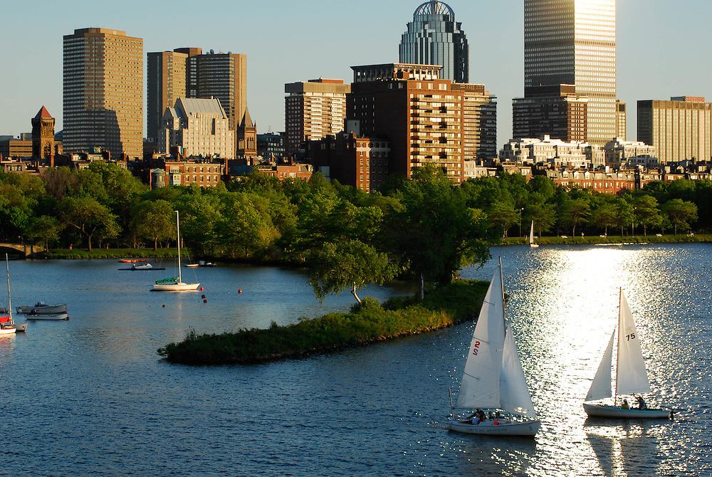 The setting sun bounces off the Prudential Tower towards sailboats on the Charles River.