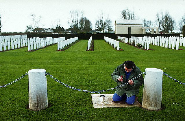 March 1994, Bayeux, France --- A caretaker paints the chain fence of the British World War II cemetery in Bayeax, France. --- Image by © Owen Franken/Corbis