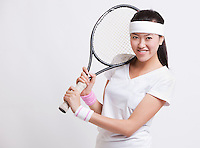 Portrait of happy female tennis player holding racket against white background