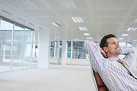Office worker leaning back in swivel chair hands behind head in empty office space