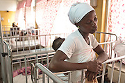 Ghana: 25 April 2012, A woman rests against a cradle at the Princess Marie Louise Children's hospital in Accra..The GAVI Alliance is a public-private partnership that brings together developing country and donor governments, WHO, UNICEF, the World Bank, the vaccine industry in both industrialised and developing countries, research and technical agencies, civil society, the Bill & Melinda Gates Foundation and other private philanthropists.  Set up in 2000 as the Global Alliance for Vaccines and Immunisation, GAVI's mission is to save children's lives and protect people's health by increasing access to immunisation in the world's poorest countries.